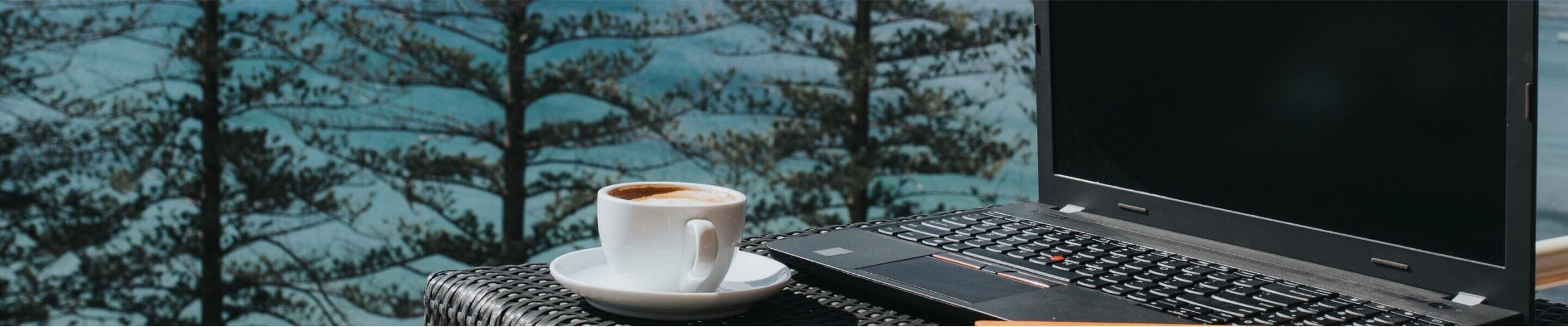 coffee cup by laptop