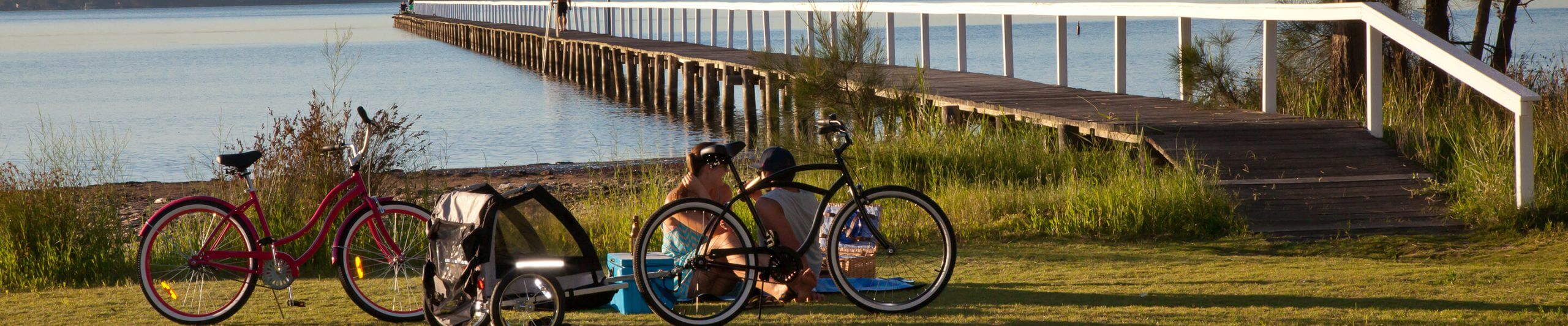 people sat near wooden pier and bikes