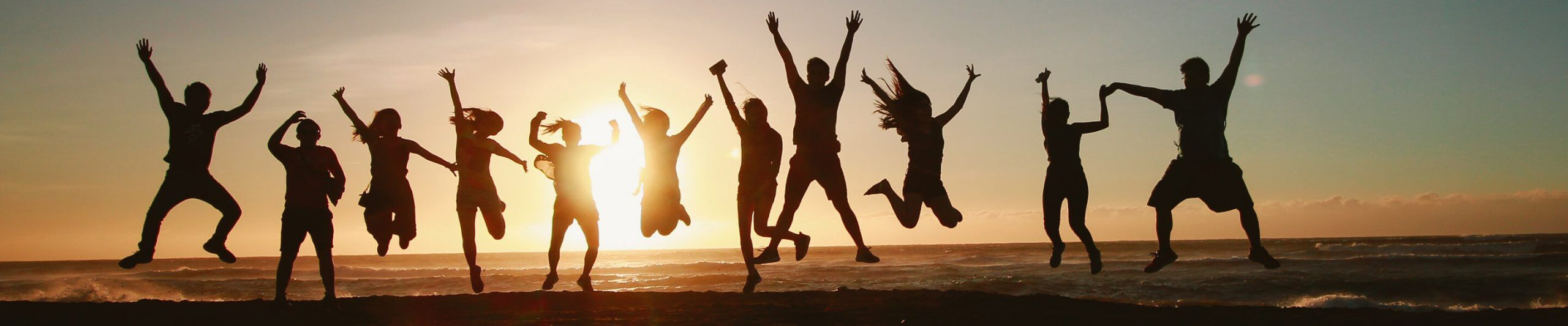 group of people jumping in air at sunset